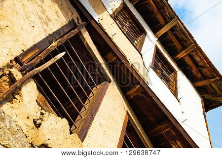 Low angle perspective looking up of an old dilapidated rustic building facade with cracked and missing plaster and rusty bars on the windows.