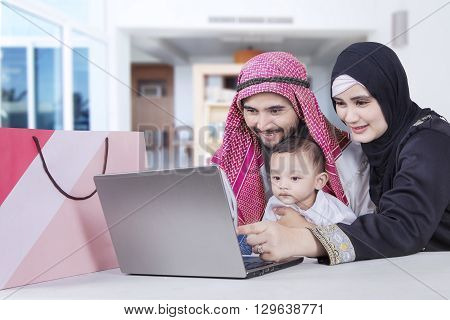 Middle eastern family shopping online with laptop in the living room at home