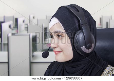 Closeup of pretty Arabian hotline operator with headphones in the office room