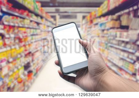 Mobile phones while shopping in a supermarket behind the blur.