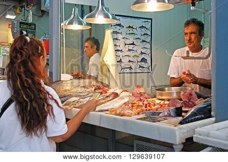 MALAGA, SPAIN - JULY 11, 2008 - Customer being served at a fish stall in the indoor market (Mercado de Atarazanas) Malaga Malaga Province Andalucia Spain Western Europe, July 11, 2008.