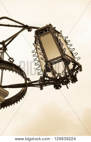 big ancient iron streetlight or lamp in retro style closeup and isolated against the sky
