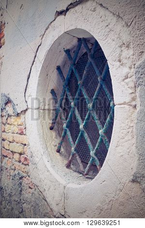 old brick facade of the ancient building with a round window and a iron lattice in retro style