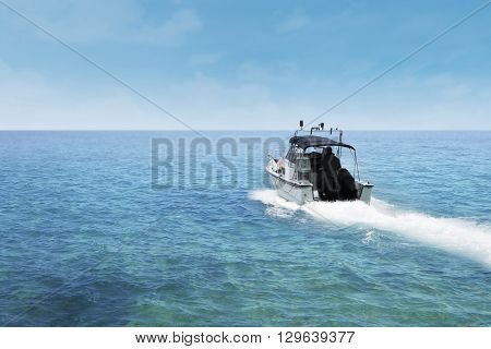 Picture of a man driving a motor boat on the blue sea at summer day