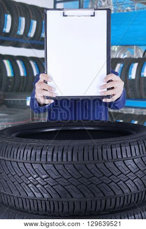 Image of a mechanic showing a clipboard with copy space in the workshop