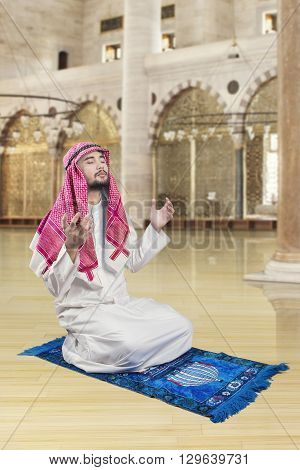 Portrait of middle eastern man sitting in the mosque while praying to the GOD