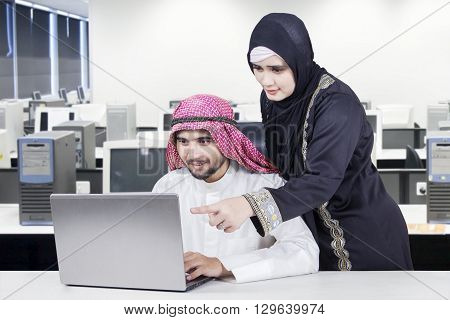 Portrait of two Arabian people looking at laptop screen together in office