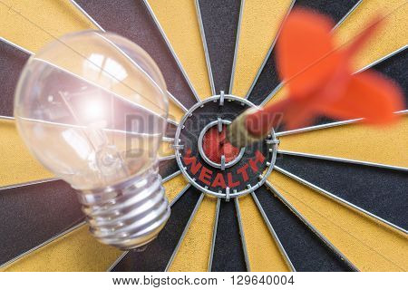 Arrow hitting the wealth bullseye target with idea lamp on dartboard Success business finance wealth profit concept symbol of successful