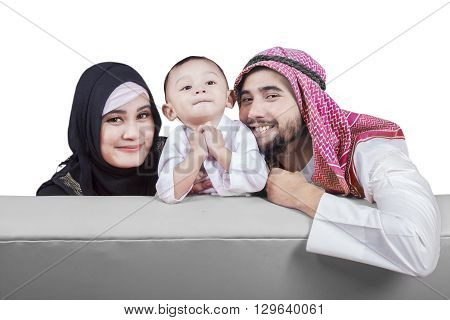 Portrait of happy muslim family with islamic clothes smiling at the camera