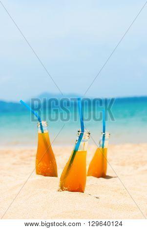 Orange Juice Bottles Straws Beach Sea Background
