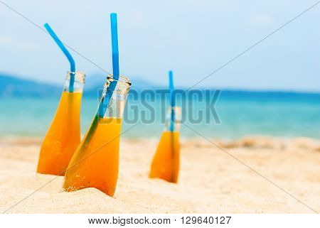 Orange Juice Bottle Sand Beach Blue Sea Background