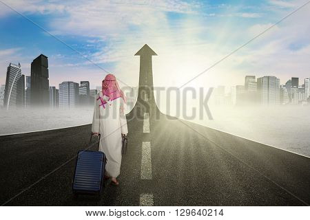 Arabian businessman carrying luggage and walking on the road turning into upward arrow