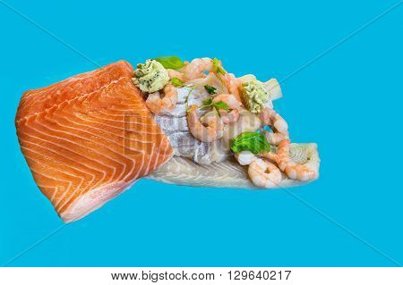 Various raw fish species as fillets like salmon cod and shrimp.