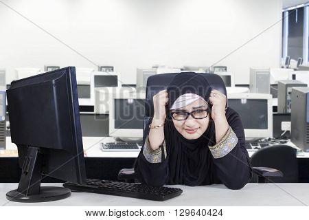 Portrait of stressful Arabian businesswoman wearing headscarf and working in the office