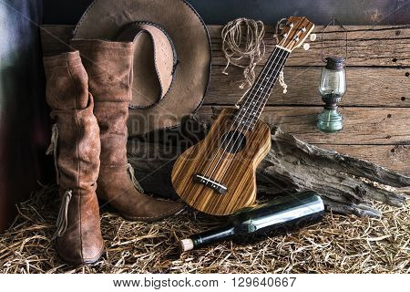 Still life photography with ukulele on american west rodeo brown felt cowboy hat and traditional leather boots in vintage ranch barn background