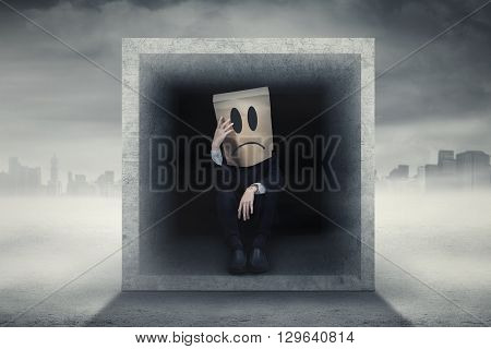 Male entrepreneur with cardboard head looks confused and sitting inside a box outdoors