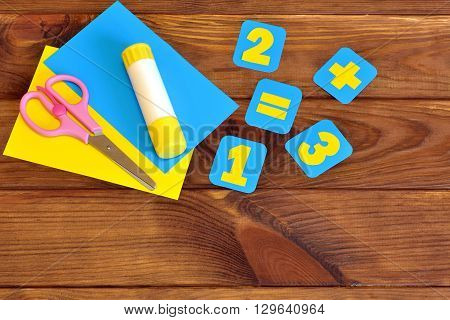 Paper cards with numbers, scissors, paper sheets, glue on a brown wooden background. Education concept