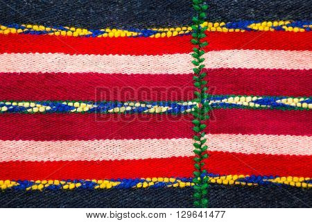 Brightly colored Bulgarian woven handmade woollen rug texture with a red and white stripes decorated with blue yellow and green patterns in a fill frame detailed view