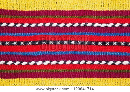 Bulgarian hand woven woollen rug with a bright multicolored striped pattern and white accents in a full frame background texture