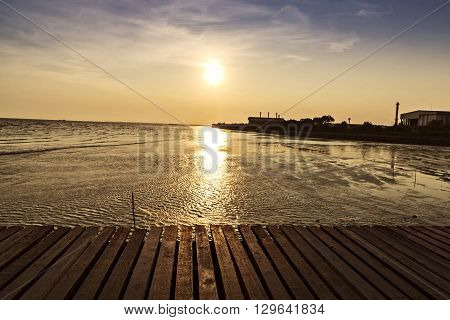 wooden bridge with beautiful sunset background above the sea, warm tone