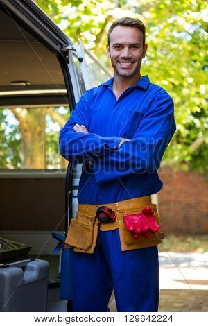 Portrait of mechanic with a tool belt around waist standing near a car