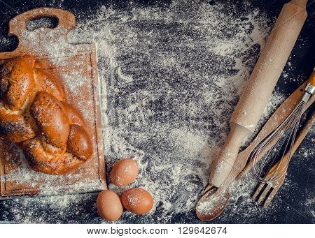 Baking concept on dark background with free text space. Top view of variety of baking utensils with eggs and baked bread on chalkboard. Composition of baking and kitchen accessories on black table.