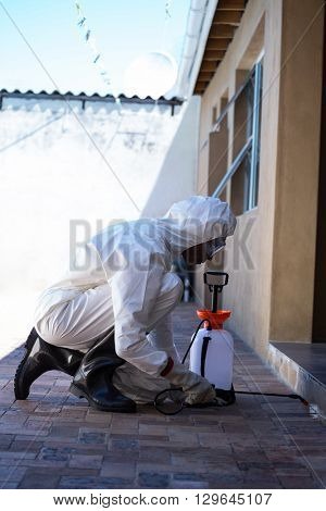 Side view of a man doing pest control at home