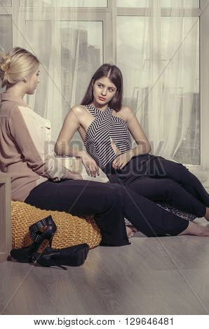 Two Girls Talking In An Informal Atmosphere