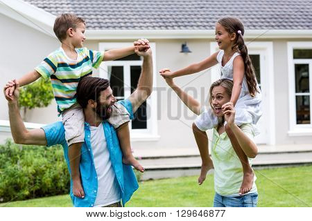 Parents carrying children on shoulder enjoying in yard