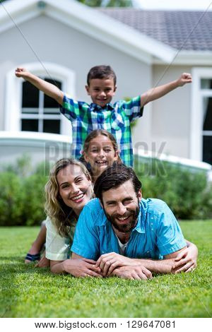 Portrait of happy family lying on top of each other over grass in yard