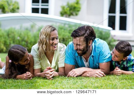 Close-up of smiling parents with children lying on grass in yard