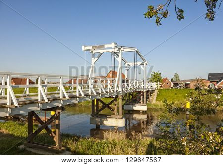 Steinkirchen, Germany - May 8, 2016: Wooden drawbridge across Luehe river in the Altes Land region of Lower Saxony in evening light, tourists with bikes on dike in background