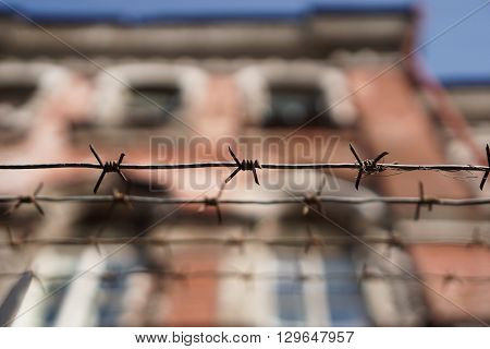Rows of barbed wire. Old brick house in the background.