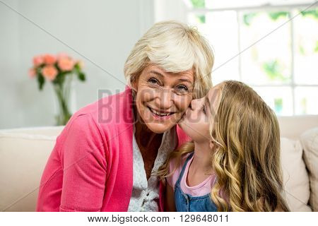 Girl kissing smiling granny while sitting on sofa