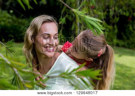 Happy mother piggybacking daughter in yard