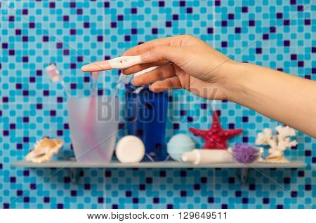 A pregnancy test in a female hand on a background of bathroom