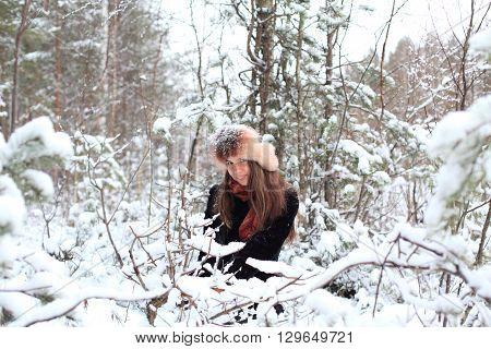 beautiful girl sitting among the snowy trees