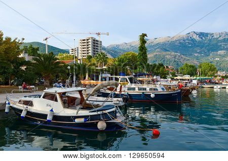 BUDVA MONTENEGRO - SEPTEMBER 15 2015: Unidentified people are relaxing on the promenade of the popular resort of Budva near the berth of pleasure boats Montenegro