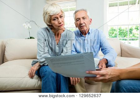 Cropped image of consultant showing report to aged couple at home