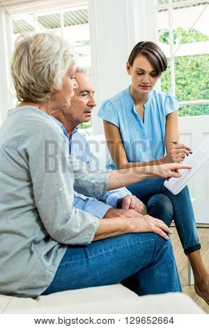 Aged couple reading report with female consultant at home