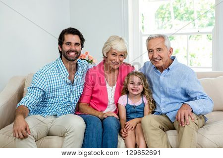 Portrait of family with grandparents sitting on sofa