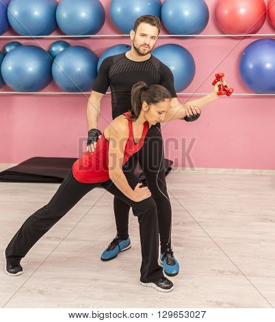 Young woman helped by her coach is training with a dumbells in a gym.