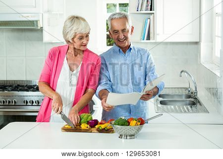 Happy senior couple with recipe book while preparing vegetables in kitchen