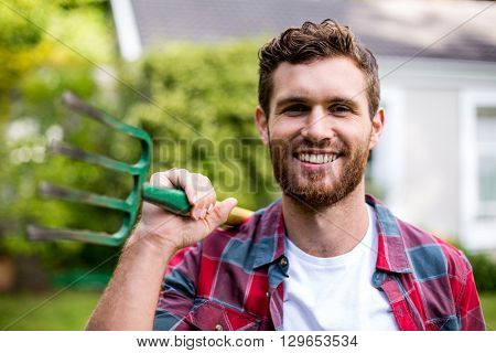 Close-up portrait of smiling man with rake standing in yard