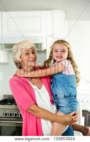 Portrait of happy granny carrying girl while standing in kitchen