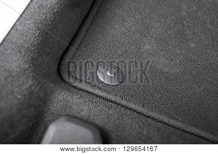 Corner of car mat with floor holder in white car interior