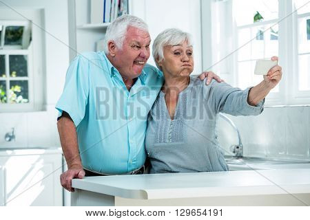 Retired couple making faces while taking selfie