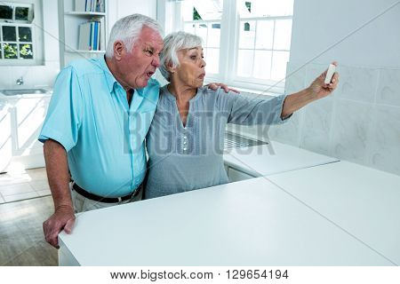 Playful retired couple taking selfie while standing in kitchen