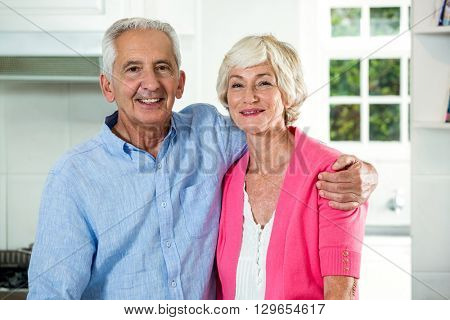Portrait of retired couple with arm around while standing at home