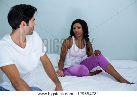 Young couple arguing on bed in bedroom at home